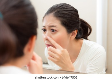 closeup photo of cute pretty lady after cleaning face looking at mirror checking nose having acne in bathroom before going to bed.