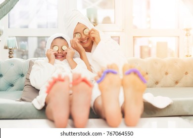 Close-up photo of daughter and mother with sponge for pedicure on fingers. Their hair is wrapped in a white bath towel. Mother and daughter put a piece of cucumber on their eyes.