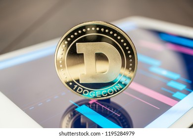 close-up photo of dogecoin cryptocurrency physical coin on the tablet computer showing stock market charts. trading dogecoin cryptocoin concept on the wooden table