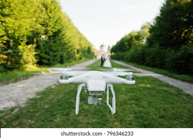 Close-up photo of a drone filming wedding couple while they walk along the alley.