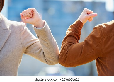 A close-up photo of elbow bumping. Elbow greeting to avoid the spread of coronavirus (COVID-19). A man and a woman meet with bare hands. Instead of greeting with a hug or handshake, they bump elbows.