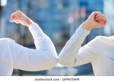 A close-up photo of elbow bumping. Elbow greeting to avoid the spread of coronavirus (COVID-19). Man and woman in shirts meet in the street. Instead of greeting with hug or handshake, they bump elbows
