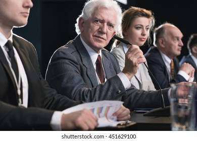 Close-up photo of an elderly man at a conference table, accompanied by other participants