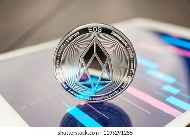 close-up photo of eos cryptocurrency physical coin on the tablet computer showing stock market charts. trading eos cryptocoin concept on the wooden table