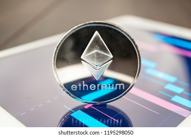 close-up photo of ether cryptocurrency physical coin on the tablet computer showing stock market charts. trading ether cryptocoin concept on the wooden table