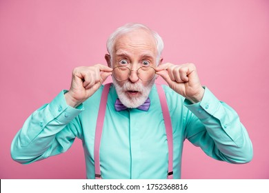 Closeup photo of excited crazy attractive grandpa open mouth listen good news astonished taking off specs wear mint shirt suspenders bow tie isolated pastel pink color background
