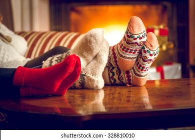 Closeup photo of family warming feet at fireplace