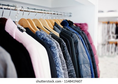 Close-up photo of fashionable clothes on hangers in the shop.