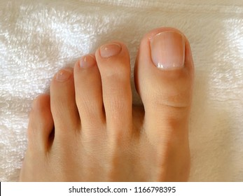 Closeup photo of woman's feet and toes on white towel