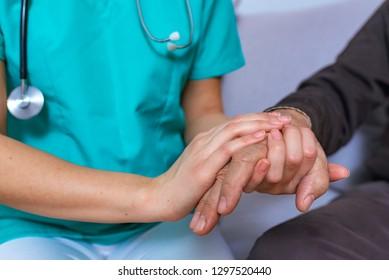 Close-up photo of a female caregiver and senior man holding hands. Senior care concept. Closeup of hands of a young woman holding hand of an senior man