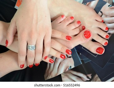 Closeup photo of a female feet and hands with beautiful red pedicure and manicure, red nails polish made in a beauty salon, all natural