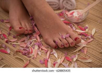Closeup photo of a female feet at spa salon on pedicure and manicure procedure