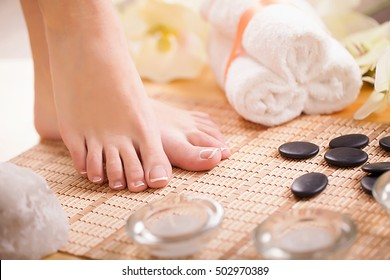 Closeup photo of a female feet with white french pedicure on nails. at spa salon. Legs care concept