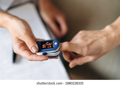 Close-up photo of a female hands. Woman doctor  measures the patient's pulse and oxygen saturation to middle aged woman using a pulse oximeter, healthcare concept