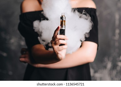Close-up photo of female holding e-cigarette with smoke. Indoors