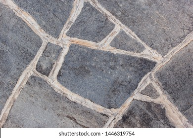 Close-up photo of flagstone patio with irregular rocks. Background, texture