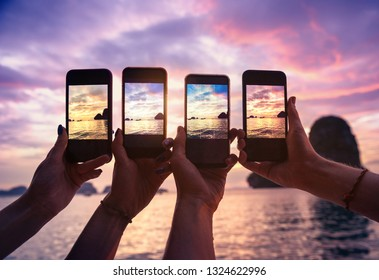 Closeup photo of four hands with mobile phones taking photo of beautiful sunset over sea bay