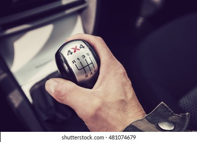 Close-up photo of four-wheel drive vehicle shifter in Finland. The photograph is also a man's hand changing gear.. Image includes a vintage effect.