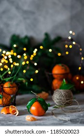 Close-up photo of fresh oranges on concreted table with blurred Christmas lights on background