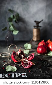 Close-up photo of fresh red pomegranates with green leaves on concreted table background
