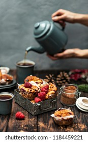 Close-up photo of fresh red raspberries with baked cupcakes on wooden table with grey teapot in female hands on blurred background