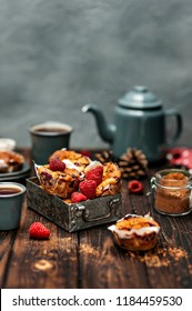 Close-up photo of fresh red raspberries with baked cupcakes with grey teapot on wooden table background