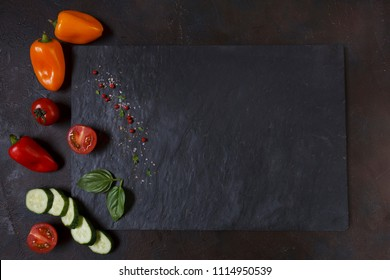 Close-up photo of fresh vegetables on black stone cutting board. Top view  on dark concreted table background