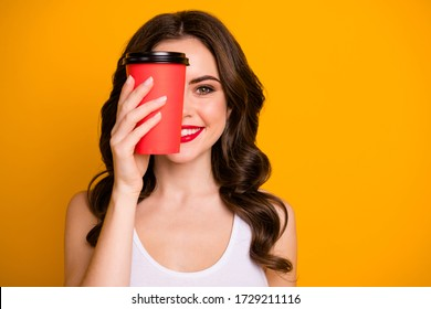 Closeup photo of funny pretty lady hold paper cup takeaway hot coffee hiding half facial expression wear casual white tank-top isolated vibrant yellow color background