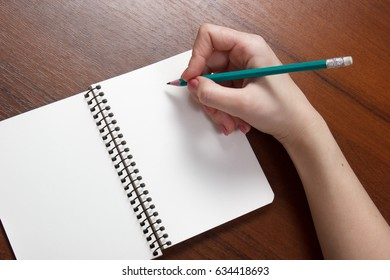 Closeup photo of girl writing in notebook with pencil