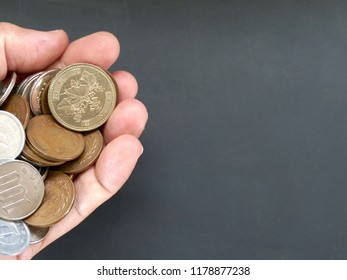 closeup photo of hand carry variety of Japanese Coin (1 , 5 , 10 , 50, 100, 500 yen coins on the background of blackboard with copy space . The concept of payment or financial concept in Japan.