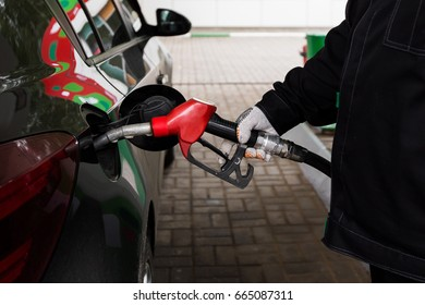 Close-up photo of hand holding fuel pump and refilling car at petrol station