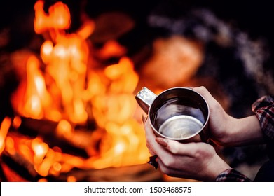 Closeup photo of hands holding camping  cup near bonfire. Ring on fingers. Mug with warm beverage. Drinking water in camp.