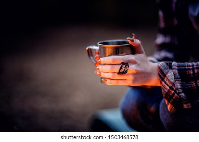 Closeup photo of hands holding camping  cup near bonfire. Ring on fingers. Mug with warm beverage.