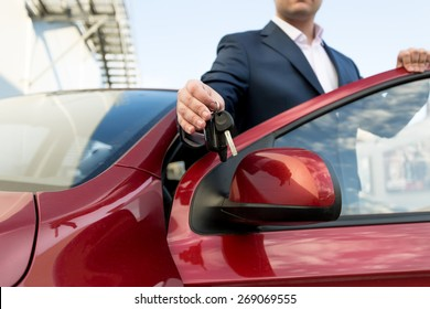 Closeup photo of handsome car salesman giving keys