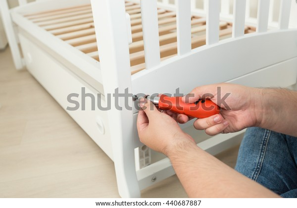Closeup photo of handyman tightening the screws on white wooden bed