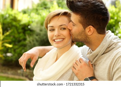 Closeup photo of happy young couple. Man kissing girlfriend.