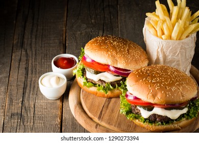 Close-up photo of home made hamburger with beer made of beef, onion, tomato, lettuce, cheese and spices. Fresh burger closeup on wooden rustic table with potato fries and chips.