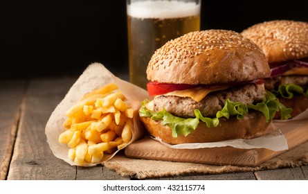 Close-up photo of home made hamburger with beef, onion, tomato, lettuce, cheese and spices. Fresh burger closeup on wooden rustic table with potato fries and chips.