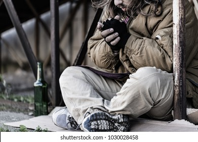 Close-up photo of homeless man sitting on the ground with an empty bottle next to him