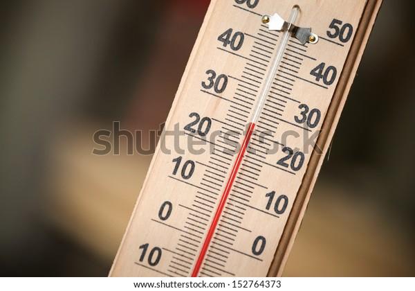 Крупным планом фото бытового спиртового термометра, показывающего температуру в градусах Цельсия