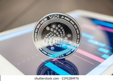 close-up photo of iota cryptocurrency physical coin on the tablet computer showing stock market charts. trading iota cryptocoin concept on the wooden table