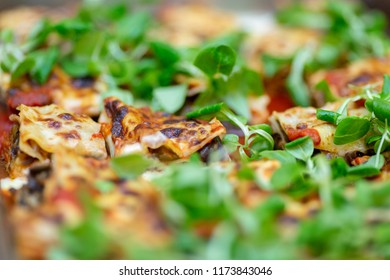 Close-up photo of italian lasagne decorated with fresh green salad leaves