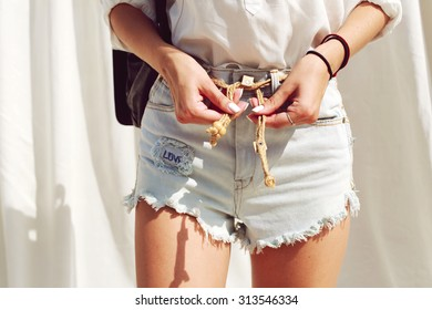 Closeup photo of jeans shorts and hand of pretty young sexy tanned girl on vacation