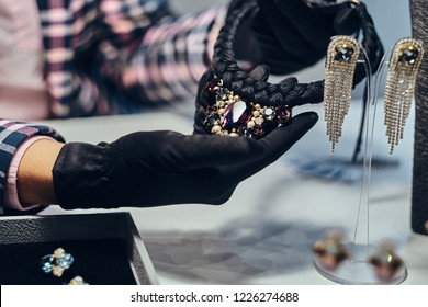 Close-up photo of a jewelry worker presenting a costly necklace with gemstones in a jewelry store.