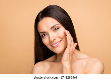 Closeup photo of latin mature nude lady natural beauty without makeup touch cheek pure soft skin applying anti age cream isolated beige pastel color background