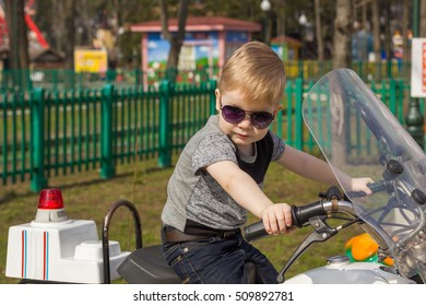 Close-up photo of little boy on the motorcycle