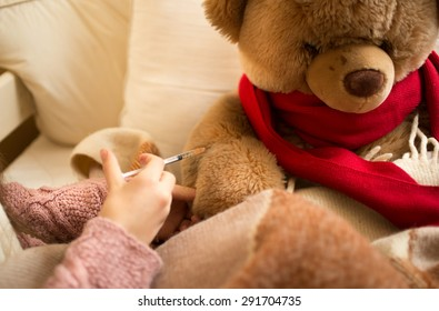 Closeup photo of little girl doing injection to sick teddy bear