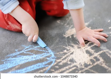 Closeup photo of little kid boy drawing with colored chalk on asphalt. Creative leisure for toddler child in summer park. Street art, kids education.