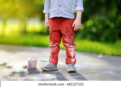 Close-up photo of little kid boy drawing with colored chalk on asphalt. Creative leisure for toddler child in summer park. Street art, kids education. Dirty clothes.