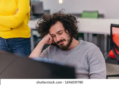 Closeup photo of a male employee with curly hair leaning on his hand on the office desk and sleeping